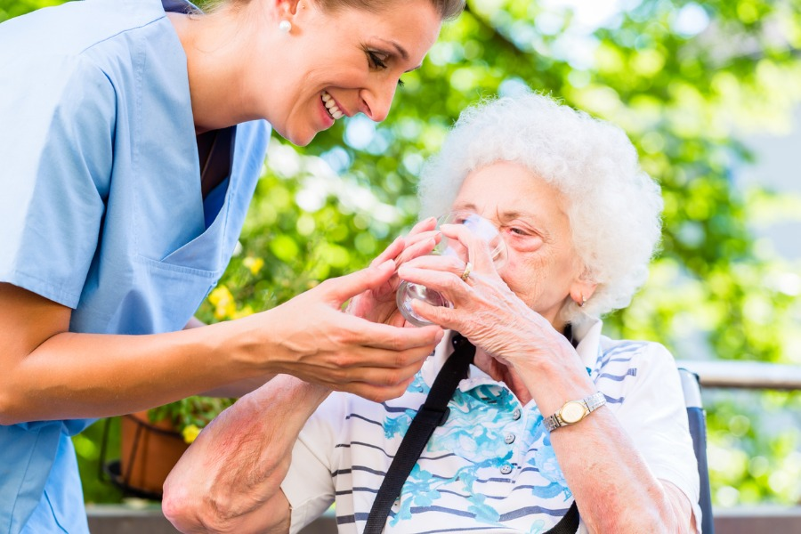 caregiver_giving_water_to_senior